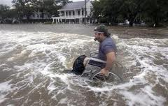 Man in a wheelchair pushing himself in two feet of flood waters