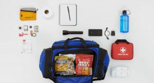 Various items are shown including a flashlight, first aid kit, water bottle, notepad and pen, packaged food in a duffle bag